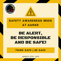 A yellow and black striped edge sign promoting safety awareness week at Auhsd.