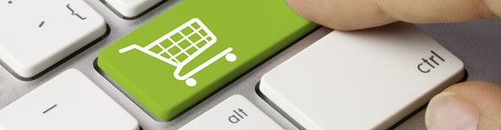 A person's finger pushing a green keyboard button with a picture of a cart on the button